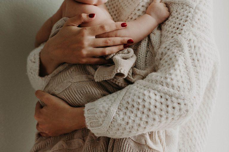 Jeune maman enveloppée dans une couverture avec son bébé