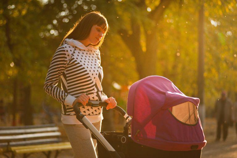 maman qui promène son enfant dans une poussette rose